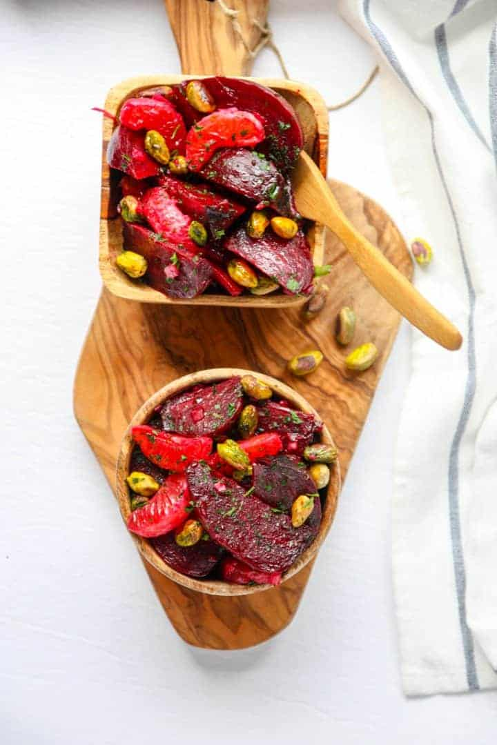 Two wooden bowls of beet, pistachio,& orange salad on a wooden cutting board