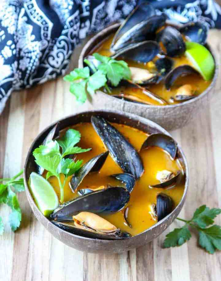 Mussels thai style in orange broth in brown wooden bowl on wooden table