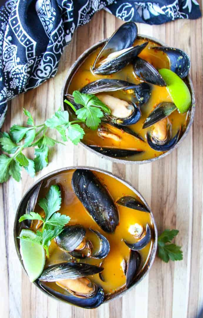 Two coconut shell bowls with mussels in the shell in a Thai curry broth with lime wedges and cilantro leaves