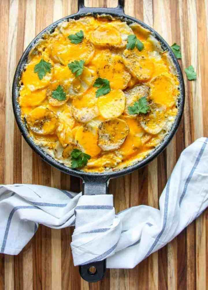 Cast iron skillet pan of baked potatoes au gratin