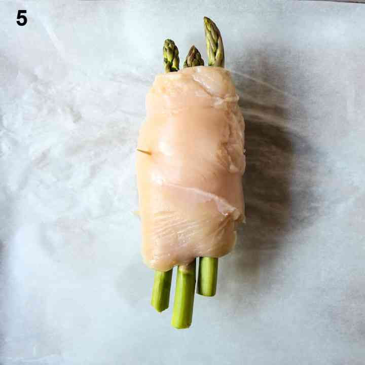 Chicken breast being wrapped around asparagus and cheese.