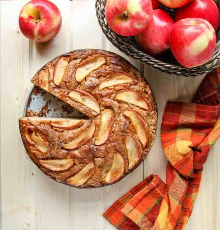 A bowl of apples sitting on a table, with a Cake