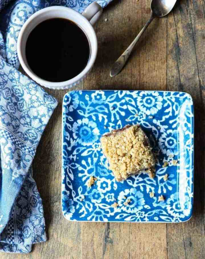 Matrimonial cake on a blue and white plate with a cup of coffee