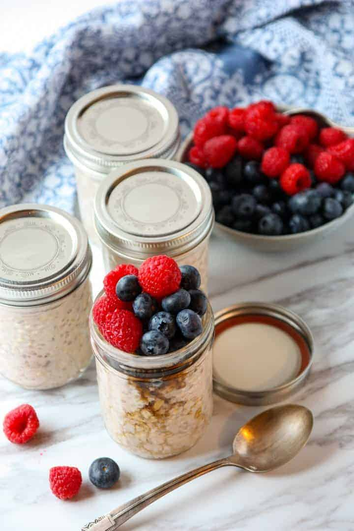 4 jars of overnight oats, 3 with lids and one topped with berries