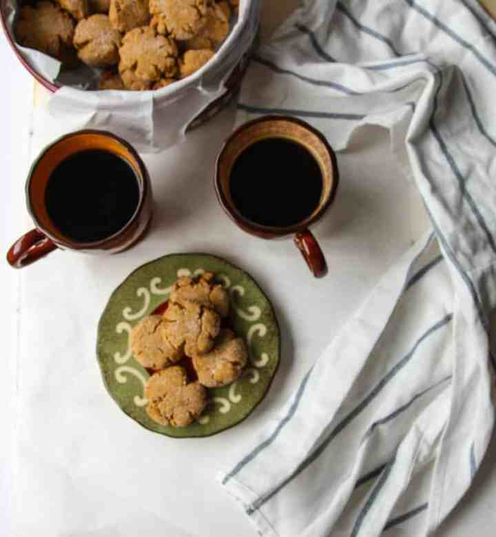 Tin of cookies with two cups of coffee and plate of cookies