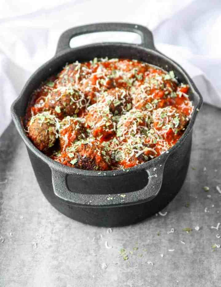 Top shot of meatballs in marinara sauce, topped with parmesan cheese in black pot