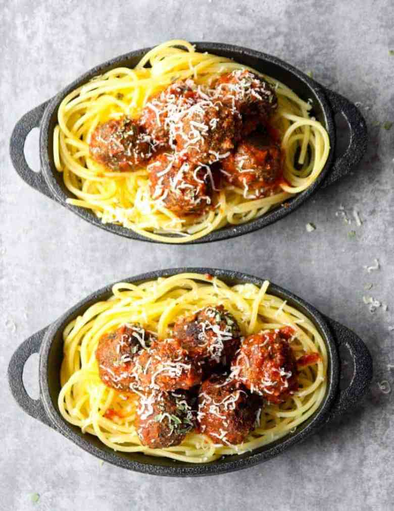Top down shot of two cast iron dishes of spaghetti topped with meatless meatballs in marinara sauce