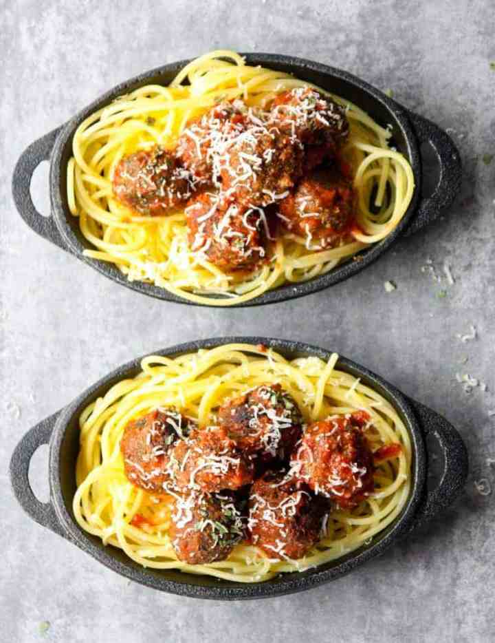 Top shot of two small black skillets with spaghetti and meatballs