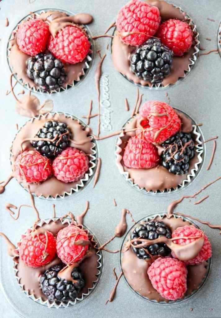 Chocolate cups with raspberries and blackberries in a mini muffin pan