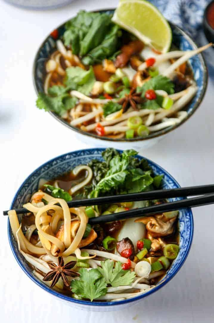 top shot of two bowls of Vietnamese soup with black chopsticks