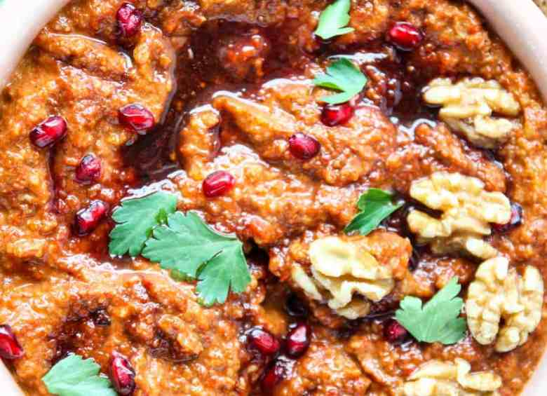 close up of muhammara, a roasted red pepper dip, topped with walnuts, pomegranate arils, and drizzled with pomegranate molasses