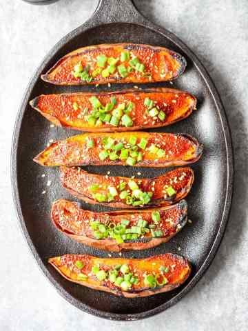 six baked sweet potato halves on a black cast iron skillet