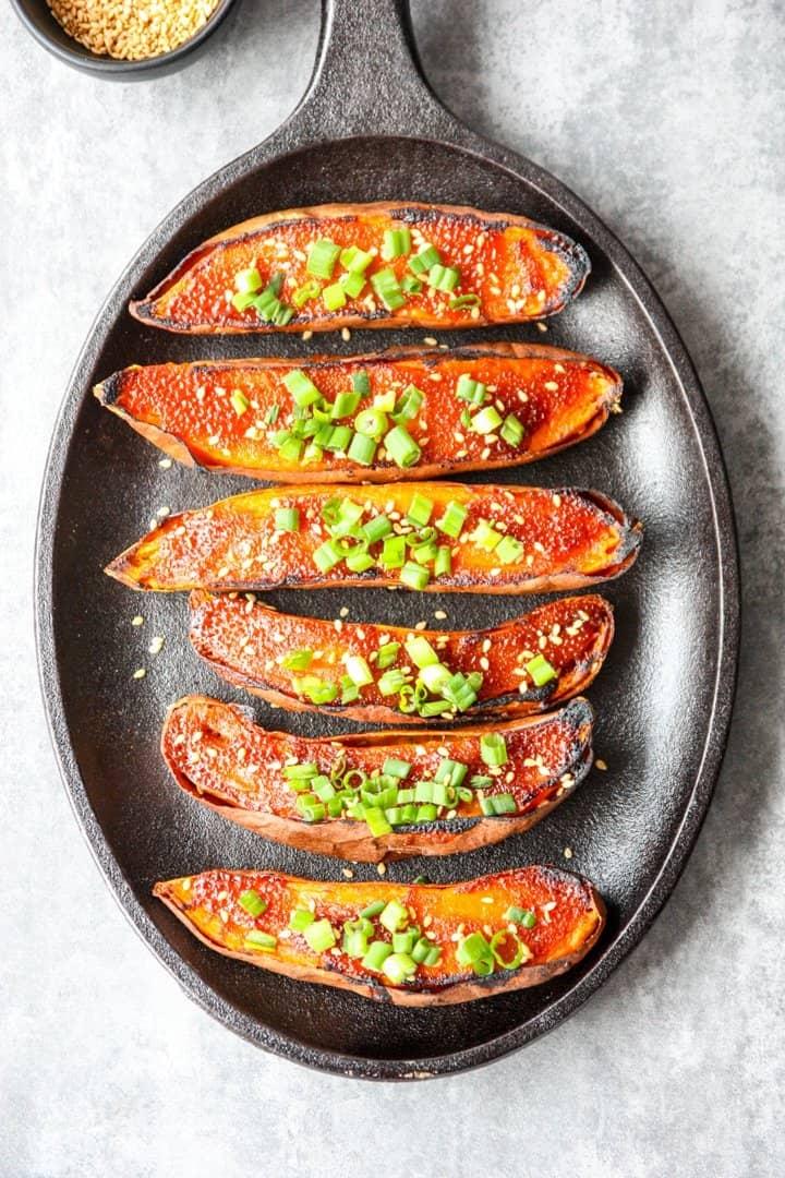 six miso baked sweet potato halves on a black cast iron skillet