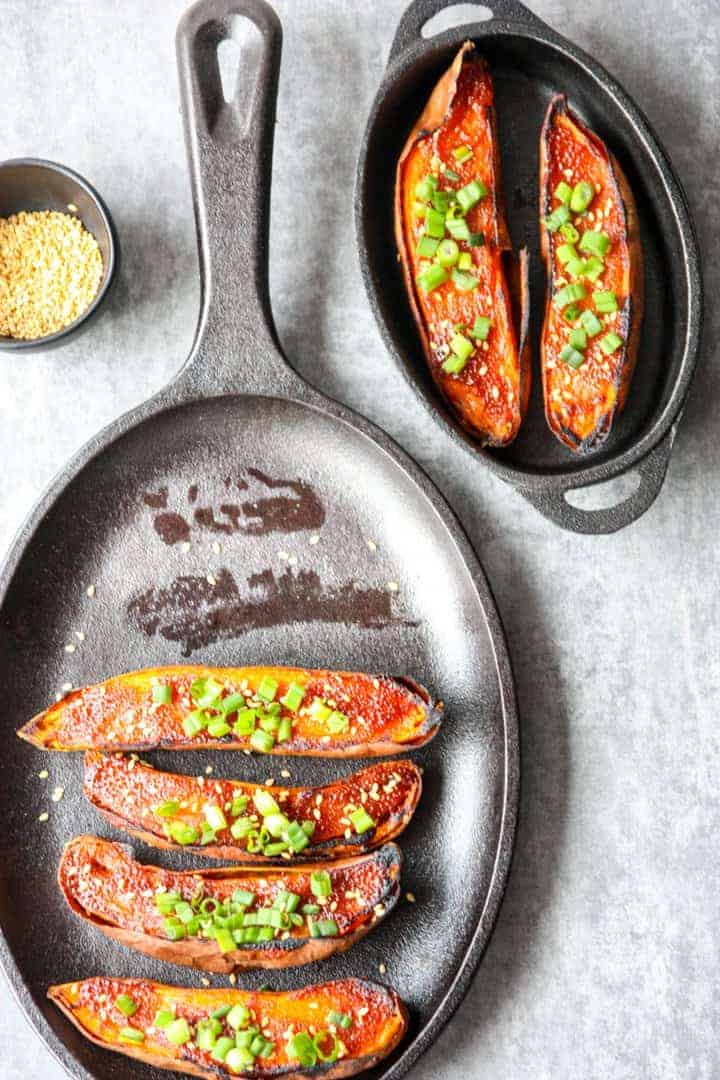 black cast iron pan with 4 miso baked sweet potato halves and a serving dish with two sweet potato halves