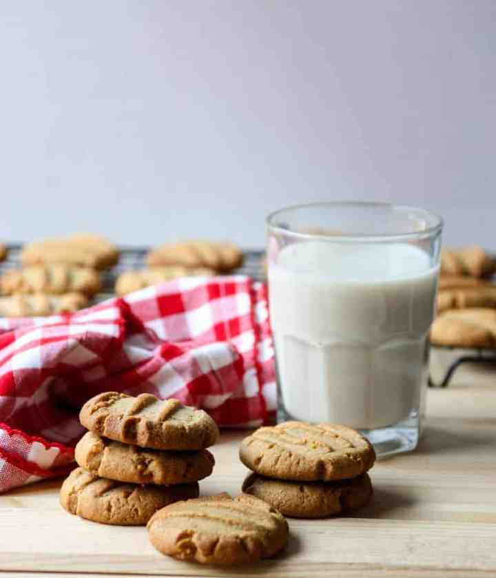 Two stacks of peanut butter cookies and a glass of milk