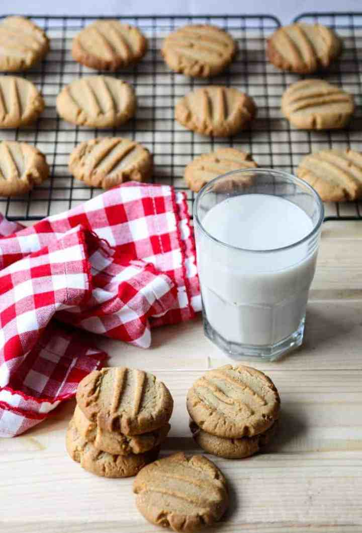 A glass of milk and tray of cookies on a table