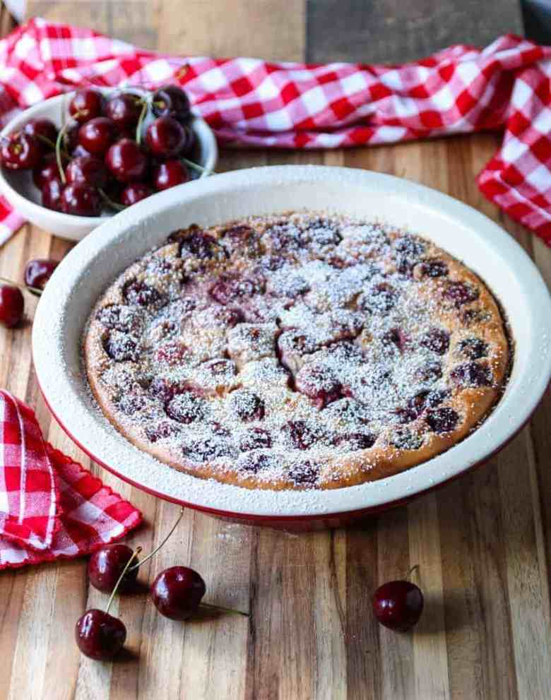 Cherry Almond Clafoutis in a white pie plate on a wooden board