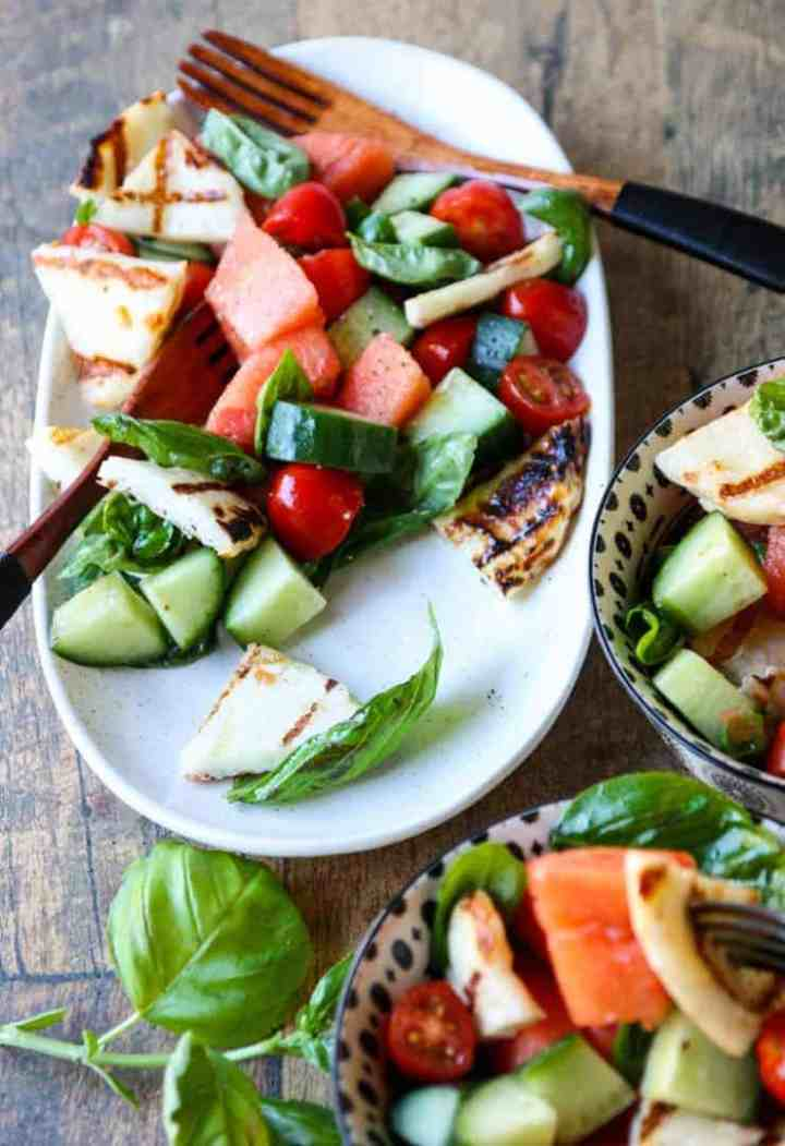 A bowl of fruit and vegetable salad on a plate, with Halloumi and Garnish