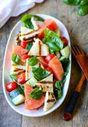 Grilled Halloumi & Watermelon Salad with tomatoes, cucumber & basil on a white platter