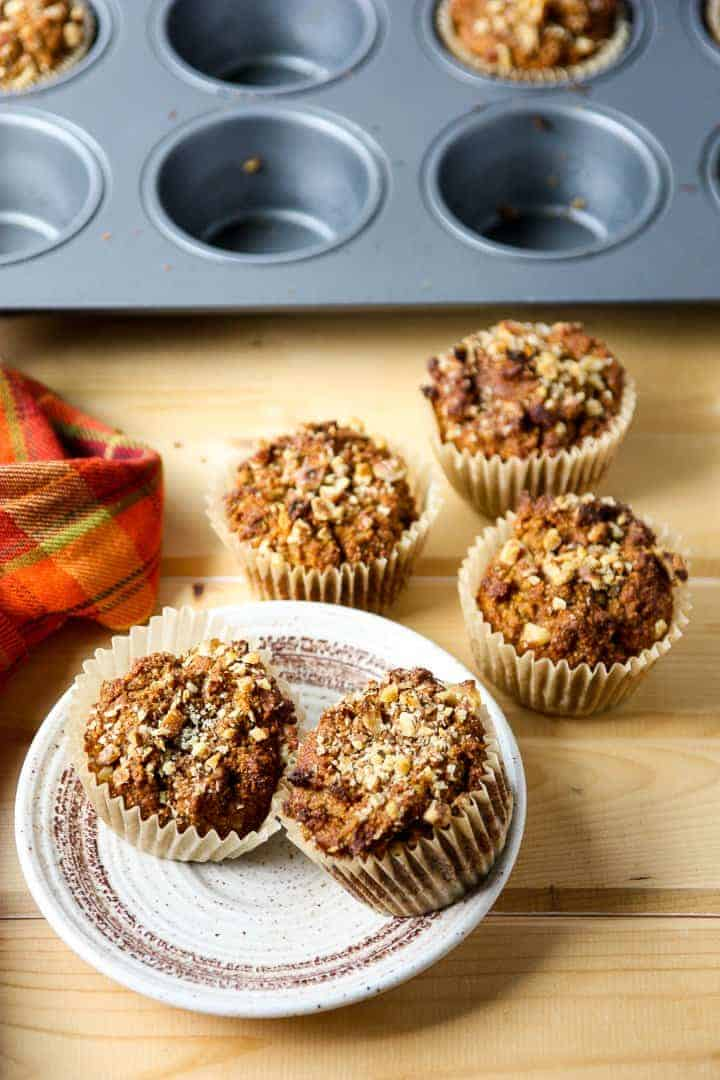 Two pumpkin pecan muffins on a white plate