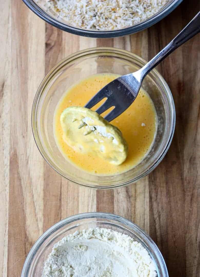 Dipping flour-dredged green tomato slice in beaten egg