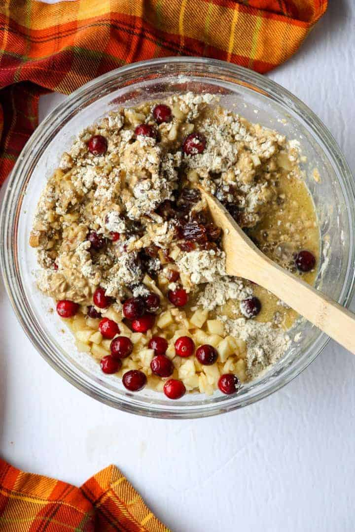 Muffin Ingredients being quickly with a wooden spoon in a glass bowl