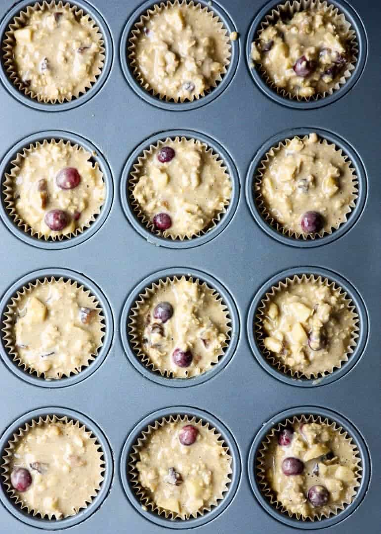 Muffin batter scooped into muffin pan cups ready to be baked