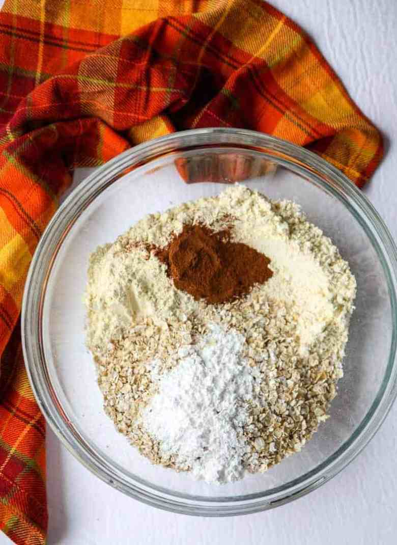 A glass bowl full of dry ingredients for making muffins, with flour, oats, and cinnamon