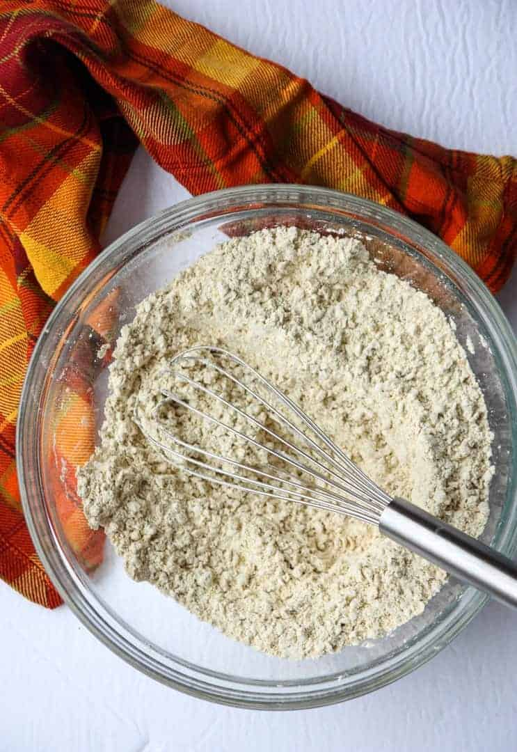 Dry ingredients for muffins are whisked together in a glass bowl