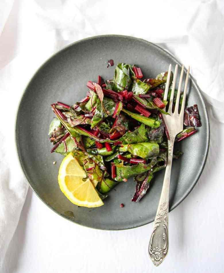 Sautéed Beet Greens on a black plate with a fork