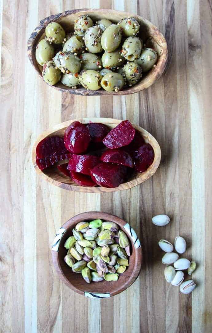 Small dishes of nuts, olives and pickles on a wooden cutting board