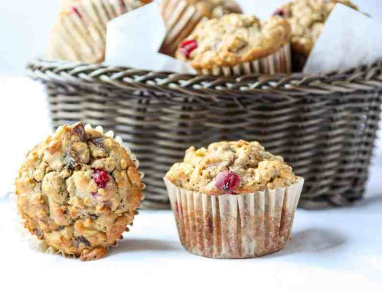 Two Apple Cranberry Muffins on a table, with a basket of muffins