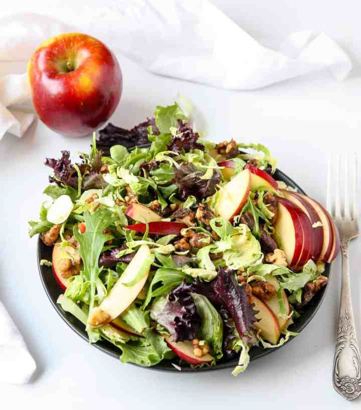 An apple and a plateful of salad on a white table with a fork.