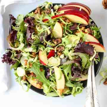 A top down view of shaved brussels sprouts and apple salad on a black plate with a fork.