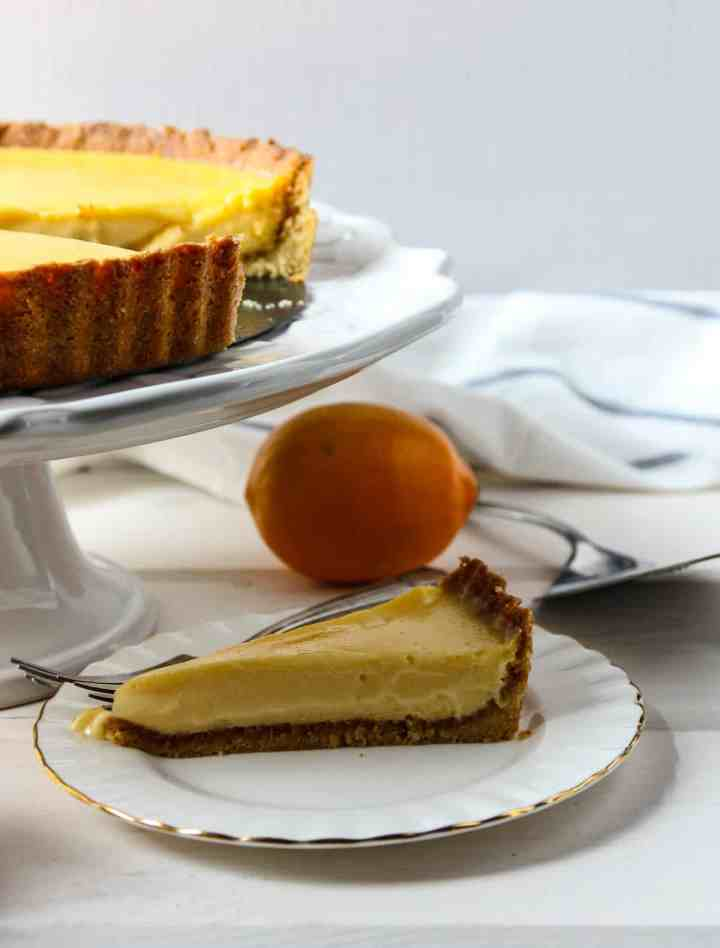 A lemon tart on a cake stand with a slice removed.