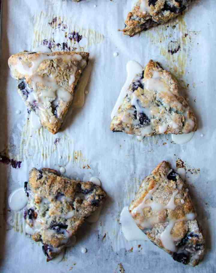 Baked scones drizzled with lemon glaze on a parchment lined baking sheet.