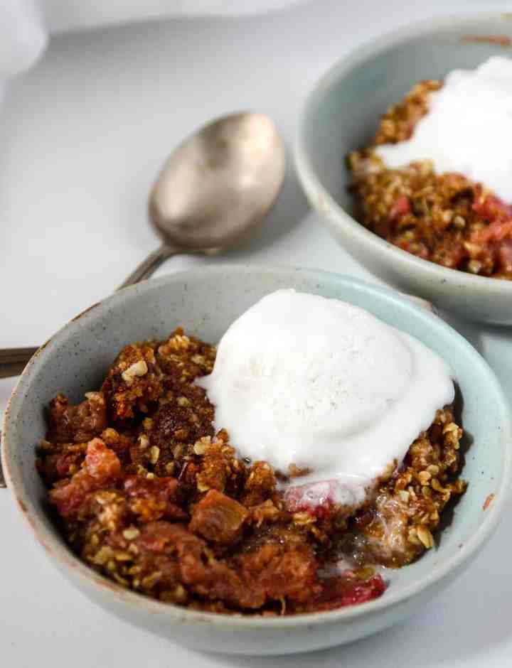Gluten Free Rhubarb Crisp in a blue bowl topped with a scoop of ice cream.