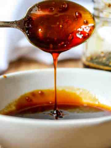 A spoon dripping with honey teriyaki sauce hovering over a white dish.