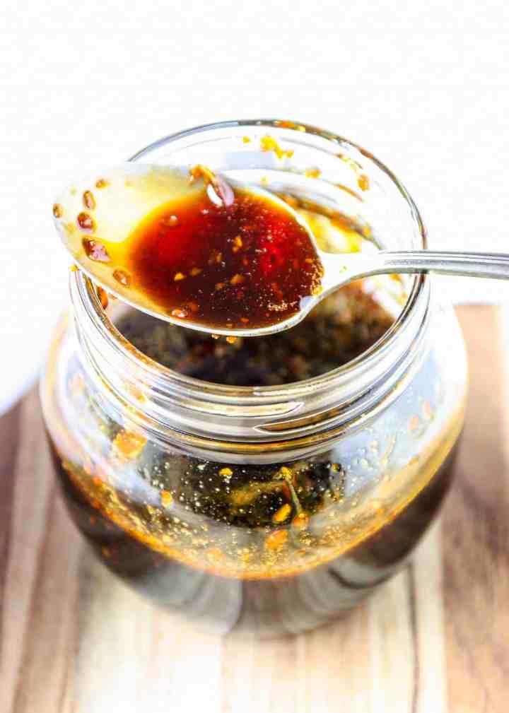A spoon resting on top of a jar of honey teriyaki sauce.