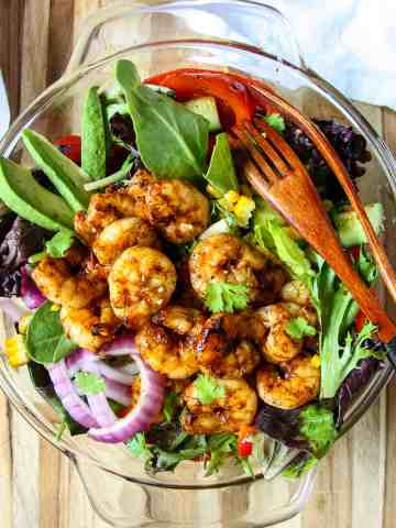 Grilled shrimp salad in a glass bowl with two wooden forks.