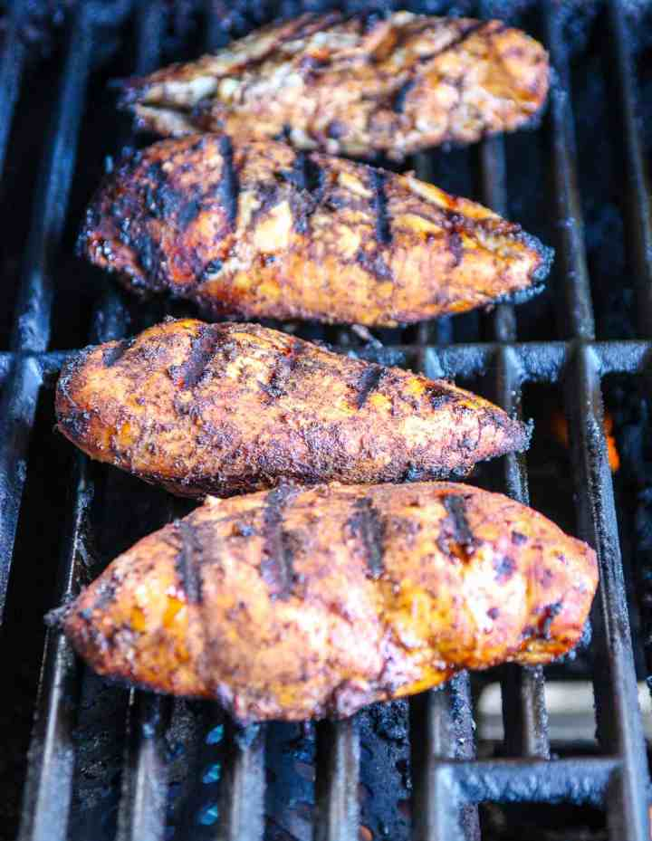 Chicken breasts cooking on a gas grill.