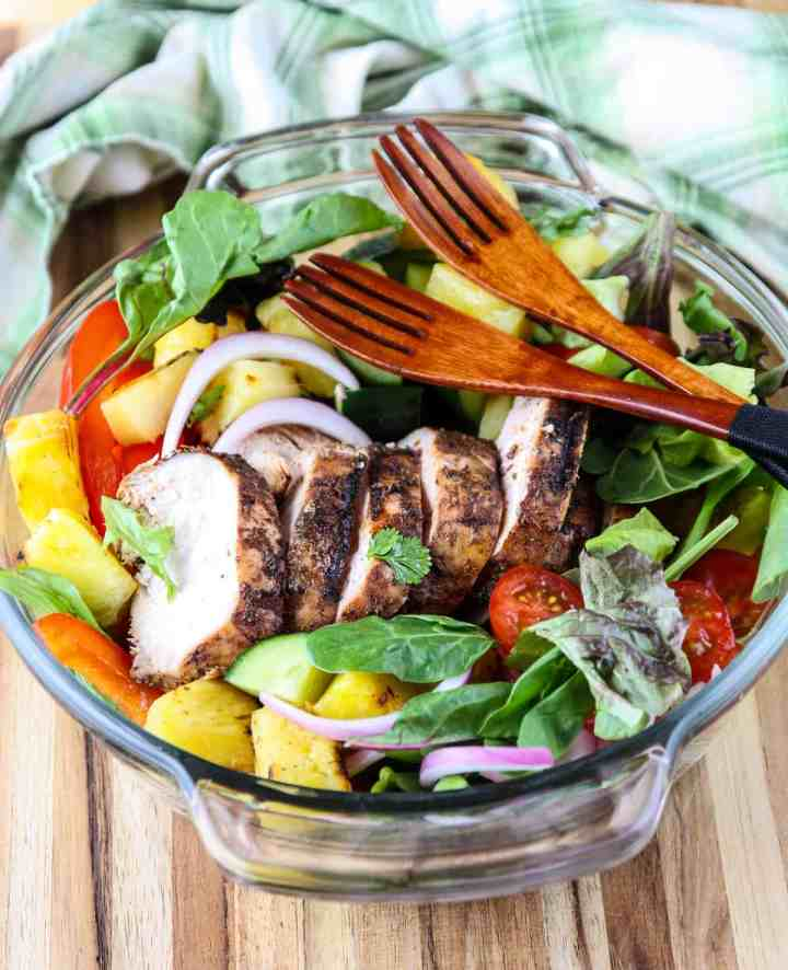 Jerk chicken salad in a glass bowl with two wooden salad forks.