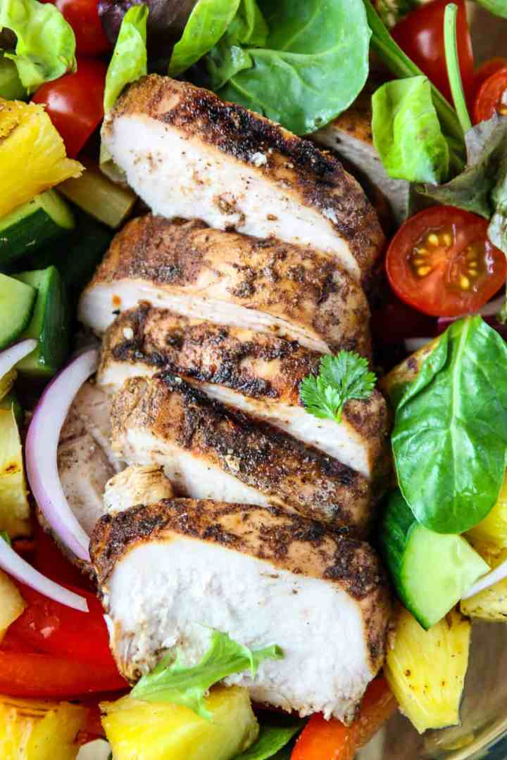 Slices of Grilled Jerk Chicken on a bed of greens.