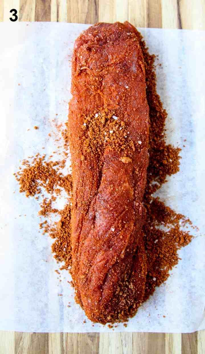 A raw pork tenderloin coated in seasoning rub.