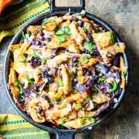 Baked nachos in a cast iron skillet.