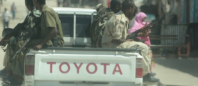 A pickup drives through Somalia's capital city, Mogadishu, with 6 armed men on the back.