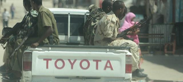 A pickup drives through Somalia's capital city, Mogadishu, with 6 armed men on the back.