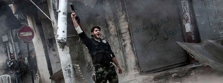 A rebel fighter signals victory after he fires a shoulder-fired missile toward a building where Syrian troops loyal to President Bashar Assad were hiding in the Jedida district of Aleppo, Syria on November 4, 2012.