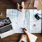 Looking at a map and laptop for wanderful inspiration
