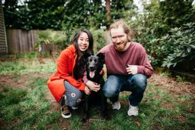 Jared and Lily (owners of the blog) taking a family photo with their black german shepherd lab dog (Grace). Frugal gene.